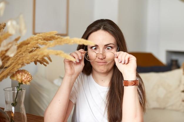 Grappige duizendjarige vrouw met een bril in de keuken van de ecostijl. trendy kleuren. natuurlijk licht Premium Foto