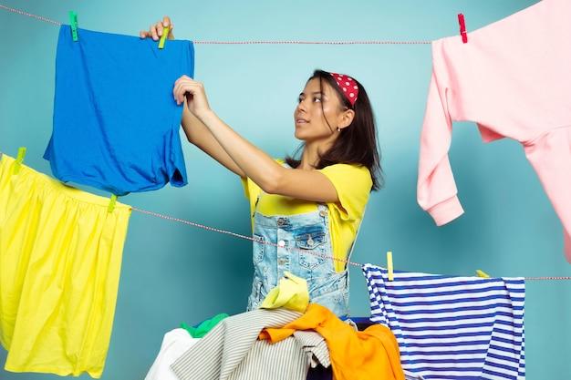 Grappige en mooie huisvrouw die huishoudelijk werk doet dat op blauwe ruimte wordt geïsoleerd Gratis Foto