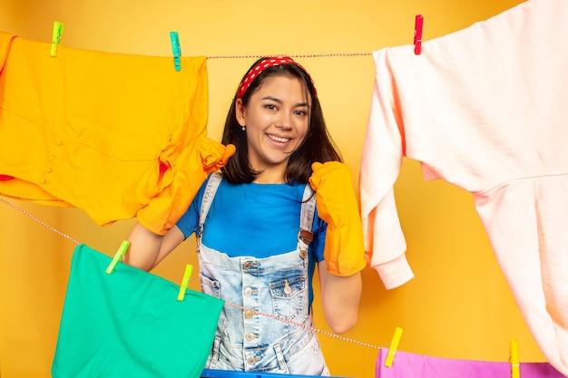 Grappige en mooie huisvrouw die huishoudelijk werk doet dat op gele ruimte wordt geïsoleerd Gratis Foto
