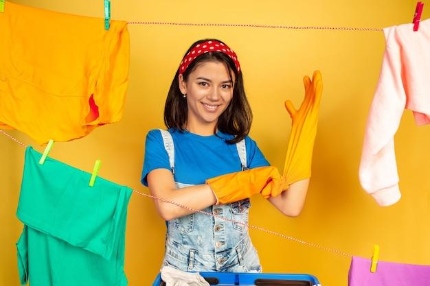 Grappige en mooie huisvrouw die huishoudelijk werk doet Gratis Foto