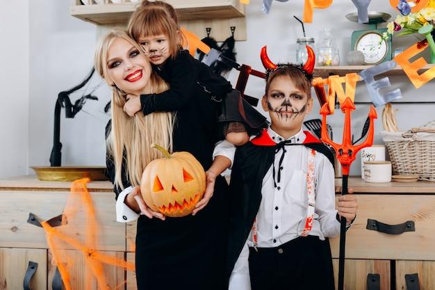 Grappige familie in de keuken die zich in kostuum bevindt en de camera bekijkt halloween Premium Foto