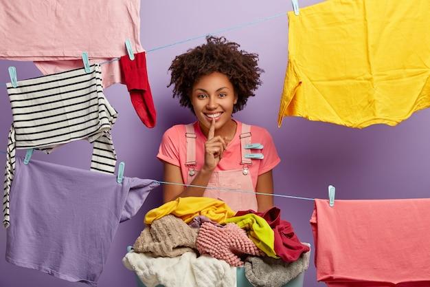 Grappige gekrulde huisvrouw vertelt geheim, glimlacht breed, maakt een zwijggebaar, wast thuis, staat in de buurt van stapel linnen, hangt gewassen kleren aan de waslijn, geïsoleerd op paarse achtergrond. Gratis Foto