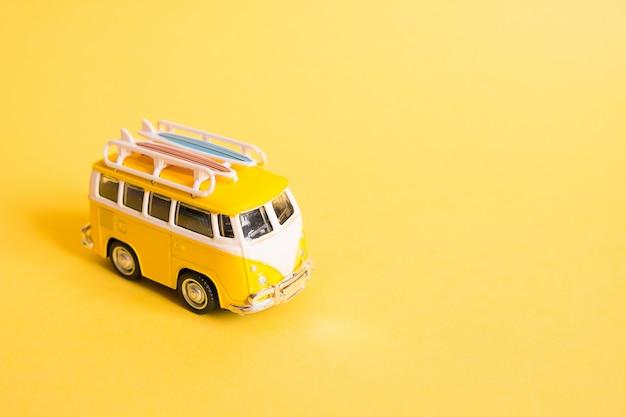 Grappige gele retro auto met surfplank op geel Premium Foto