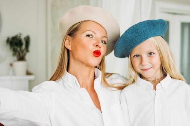 Grappige gelukkige eerlijke lange haarmamma en leuke dochter die selfie samen op mobiele telefoon bij woonkamer maken, gelukkige familielevensstijl Premium Foto