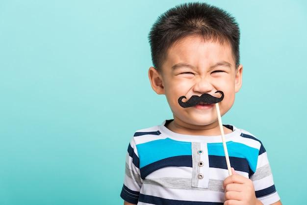 Grappige gelukkige hipster jongen met zwarte snor rekwisieten voor de fotocabine dicht gezicht Premium Foto