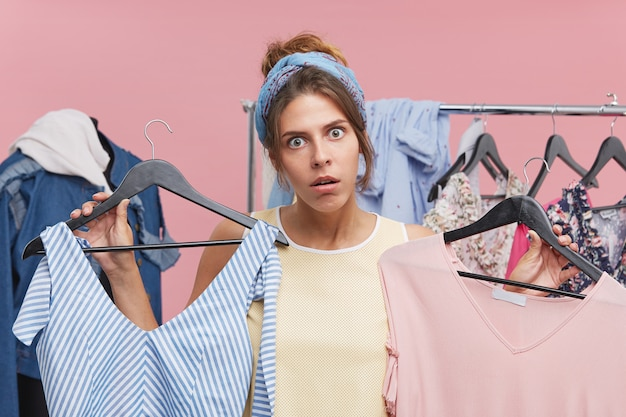 Grappige geschokte jonge vrouw die hoofdband draagt die twee hangers met modieuze kledingstukken in elke hand houdt die een wens heeft om beide te kopen terwijl het winkelen in opslag in grote verkoop. consumentisme concept Gratis Foto