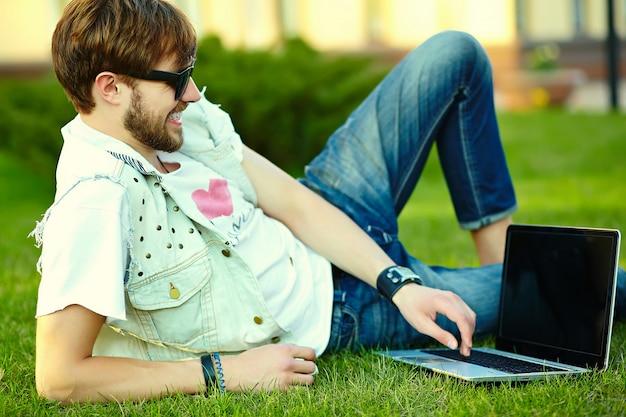 Grappige glimlachende hipster knappe mensenkerel in modieuze de zomerdoek in gras met notitieboekje Gratis Foto
