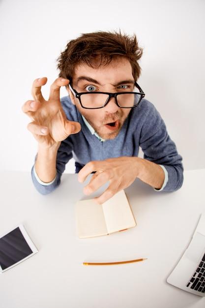 Grappige grimassen mannelijke werknemer, kantoor werknemer dwaas rond op het werk, monster klauw met hand maken en staren Gratis Foto