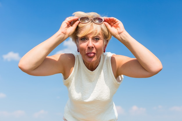 Grappige hogere vrouw haar tong uitsteekt terwijl buitenshuis poseren Premium Foto