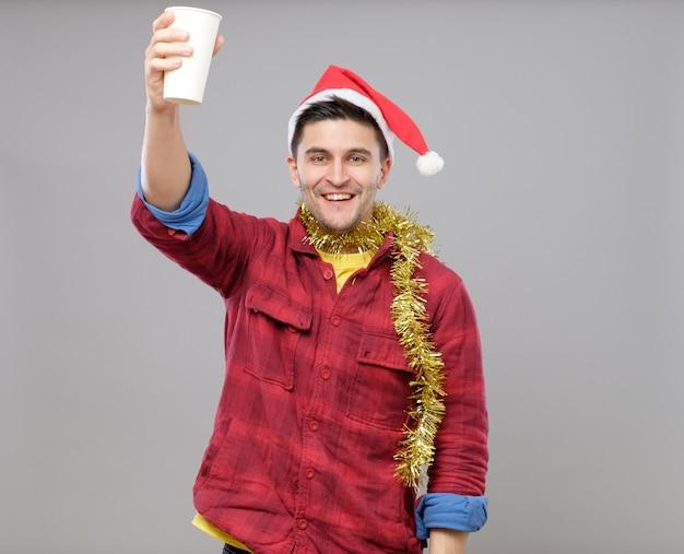 Grappige jonge dronken man met kerstmuts met een papieren beker Premium Foto