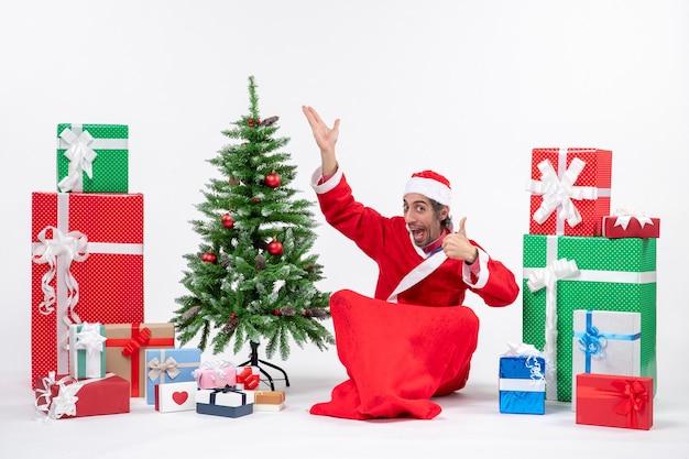 Grappige jonge volwassene verkleed als kerstman met geschenken en versierde kerstboom zittend op de grond wijzend boven perfect gebaar maken op witte achtergrond Gratis Foto