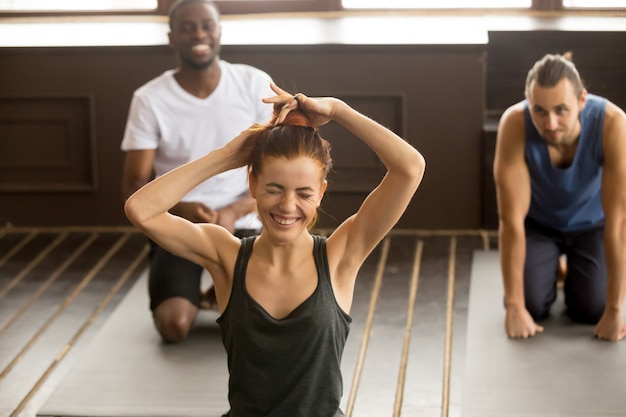 Grappige jonge vrouw die bij multi-etnische de yogacl van de groepsgeschiktheid lachen Gratis Foto