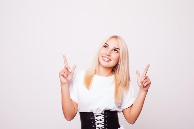 Grappige jonge vrouw in wit overhemd die geïsoleerde vinger benadrukken. tiener blond meisje grimas maken en opzoeken Gratis Foto