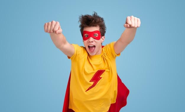 Grappige jongeman in superheld cape en masker mond openen en balde vuisten tijdens het vliegen naar camera tegen blauwe achtergrond Premium Foto