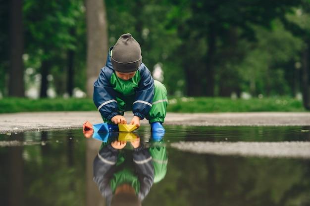 Grappige jongen in regenlaarzen spelen in een regenpark Gratis Foto