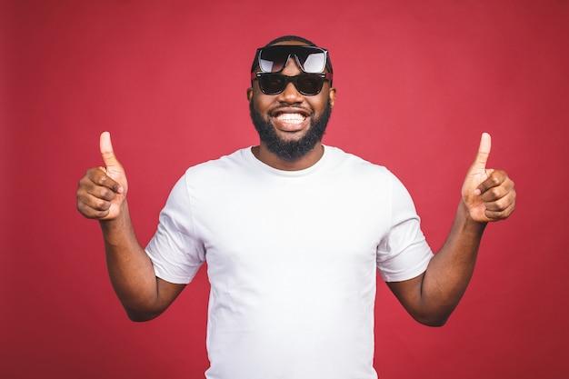 Grappige kerel in wit t-shirt en zon glases springen en kijken naar de camera. studioportret van het emotionele afrikaanse mannelijke model stellen op rode achtergrond. duimen omhoog. Premium Foto