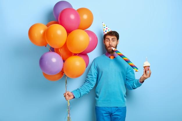 Grappige kerel met verjaardagshoed en ballonnen poseren in blauwe trui Gratis Foto