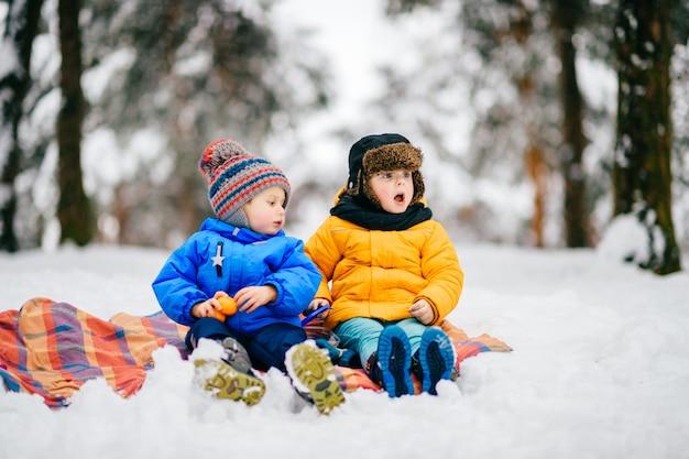 Grappige kinderen met expressieve gezichten hebben winterfeest in besneeuwde bossen Premium Foto