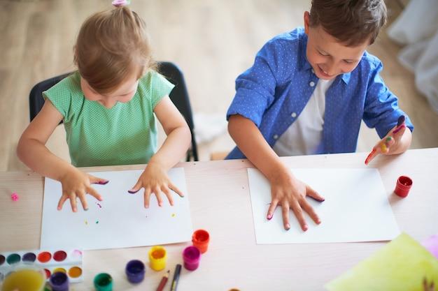Grappige kinderen tonen hun handpalmen de geschilderde verf. Premium Foto
