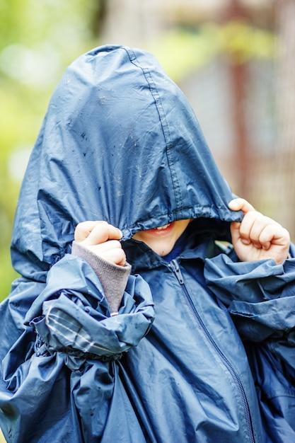 Grappige kleine jongen loopt in de regen in een regenjas met capuchon buitenshuis Premium Foto