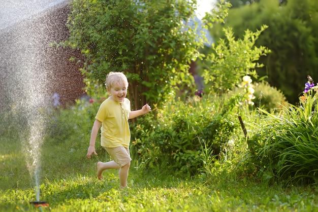 Grappige kleine jongen spelen met tuin sprinkler in zonnige achtertuin Premium Foto