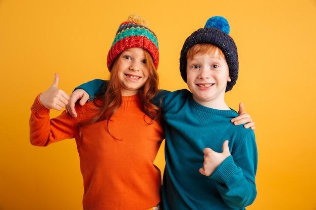 Grappige kleine kinderen dragen warme hoeden duimen opdagen. Gratis Foto
