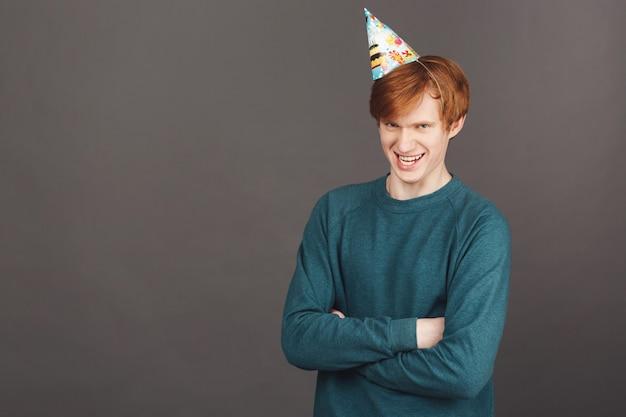 Grappige knappe jonge roodharige mannelijke student in stijlvolle groene sweatshirt en feestmuts kruising handen met dwaze uitdrukking Gratis Foto