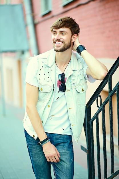 Grappige lachende hipster knappe man man in stijlvolle zomer doek in de straat in zonnebril Gratis Foto