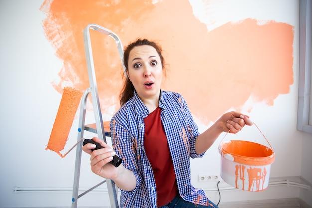 Grappige lachende vrouw schilderij binnenmuur van huis met verfroller. herinrichting, renovatie Premium Foto