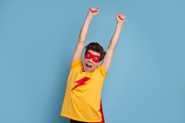 Grappige man in superheld masker schreeuwen en armen opheffen tijdens het vieren van de overwinning tegen blauwe achtergrond Premium Foto