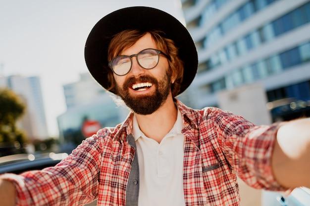 Grappige mens die met baard zelfportret door camera maken terwijl hij in grote moderne stad in azië reist. Gratis Foto