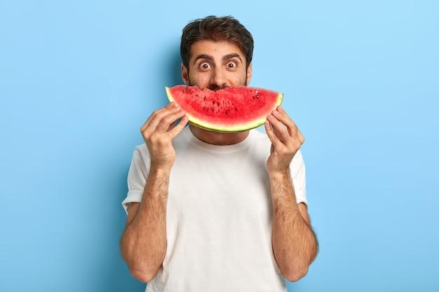 Grappige mens die op een zomerdag een plakje watermeloen houdt Gratis Foto