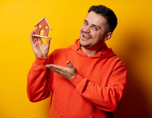 Grappige mens met stuk speelgoed huis op gele muur Premium Foto