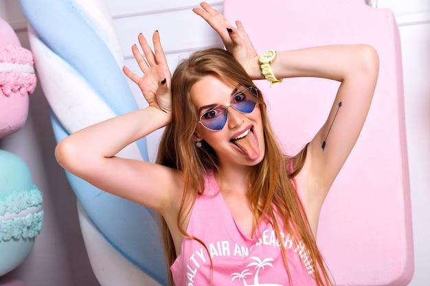 Grappige mooie gekke vrouw die zich voordeed op de muur van grote kleurrijke nep-snoepjes, grimas gezicht maken, tong tonen. heldere emoties, trendy roze kleding, gelukkig blond meisje Gratis Foto