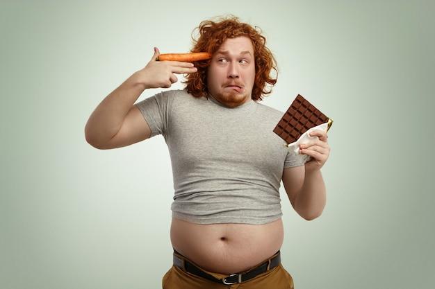 Grappige overgewicht man met reep chocolade in de ene hand en wortel bij tempel als pistool Gratis Foto