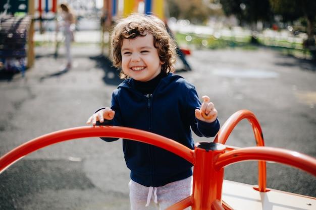 Grappige schattige gelukkig baby spelen op de speelplaats. de emotie van geluk, plezier, vreugde. glimlach van een kind. Premium Foto