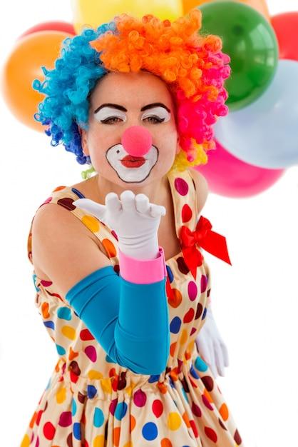 Grappige speelse vrouwelijke clown in het kleurrijke pruikenlucht kussen. Premium Foto