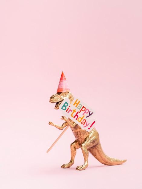 Grappige stuk speelgoed dinosaurus die gelukkig verjaardagsteken houden Gratis Foto