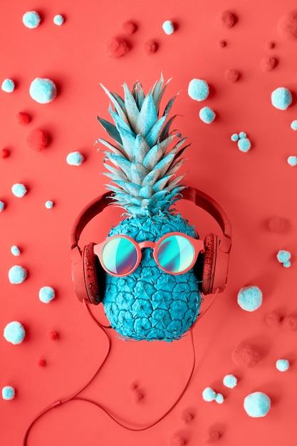 Grappige turquoise ananas in zonnebril en koptelefoon op versierd rood papier Premium Foto