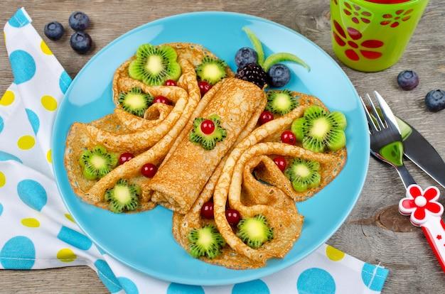 Grappige vlindergezichtspannenkoekjes met bessen en fruit voor snacks voor kinderen Premium Foto