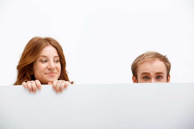 Grappige volwassenen roodharige man en vrouw verstopt achter tafel Gratis Foto