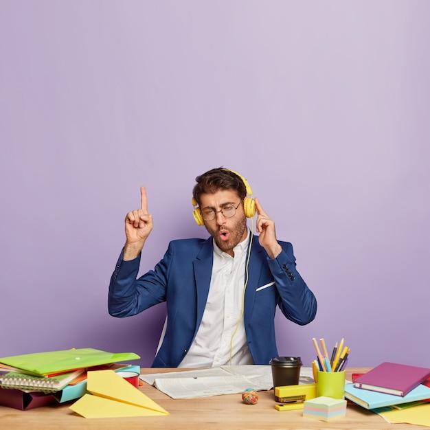 Grappige vrolijke succesvolle zakenman zit aan het bureau Gratis Foto