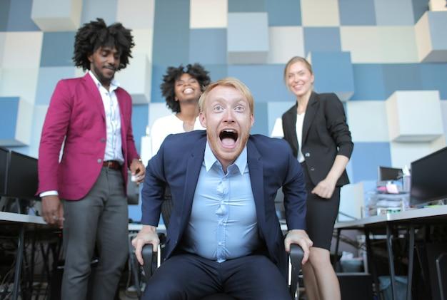 Grappige zakelijke teamleider die gelukkig schreeuwt na een productieve ontmoeting met zijn multi-etnische collega's Gratis Foto