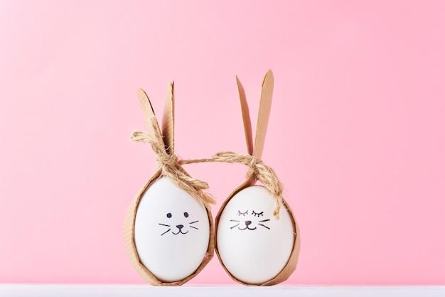 Grappige zelfgemaakte eieren met gezichten op een roze oppervlak. pasen of gelukkig paarconcept Premium Foto