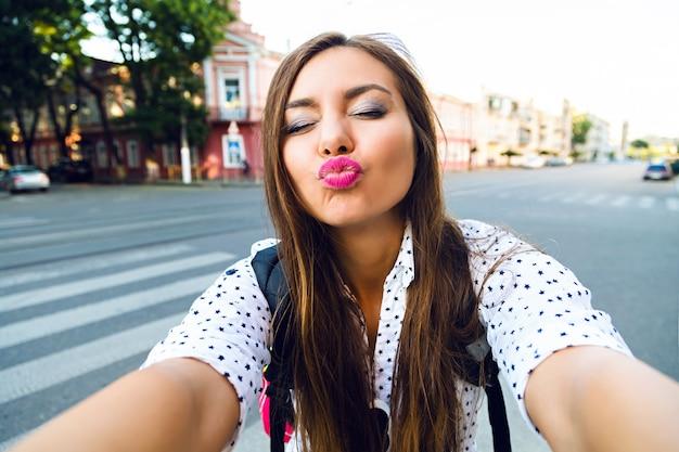 Grappige zomer foto van jonge mooie reiziger meisje selfie maken op straat, kus naar u, positieve stemming verzenden Gratis Foto