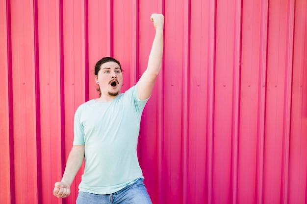 Grappigste jonge man balde zijn vuist tegen roze gegolfde metalen achtergrond Gratis Foto