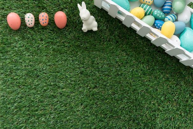 Gras achtergrond met gekleurde eieren en paashaas Gratis Foto