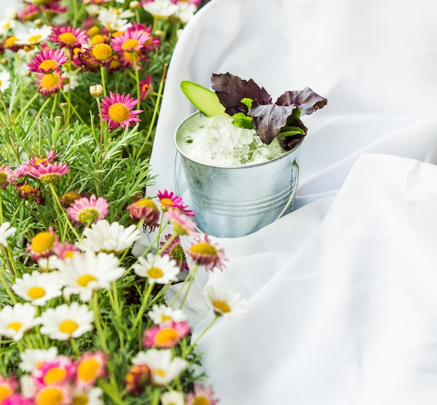 Gras met bloemen, picknicktafelkleed en een kopje yoghurt met kruiden. Gratis Foto