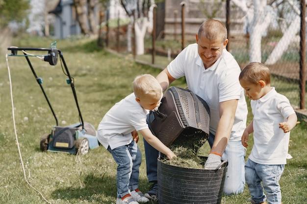Grasmaaier man aan het werk op de achtertuin met zonen Gratis Foto