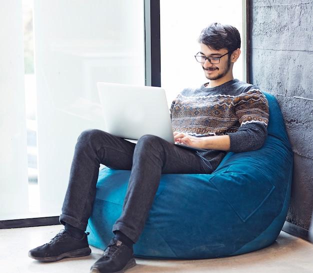 Gratis kantoorruimte, mannelijke werknemer zat naast een raam met zijn laptop Gratis Foto